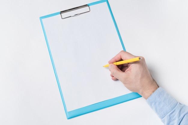 Männliche hand mit stift auf einem leeren blatt papier. mann bringt unterschrift auf papier.