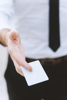Männliche hand mit weißer leerer visitenkarte, nahaufnahmefoto mit selektivem fokus