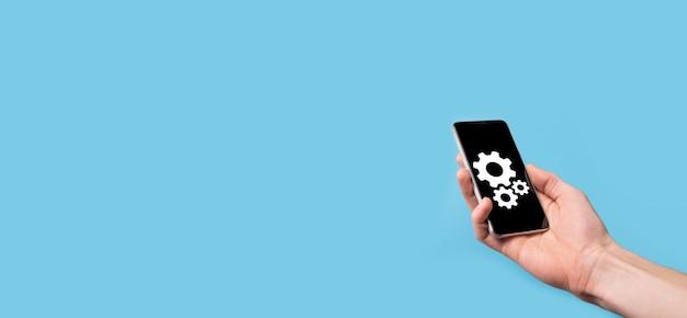 Männliche hand mit zahnradsymbol, mechanismussymbol auf virtuellen bildschirmen auf blauem hintergrund. automatisierungssoftware-technologie-prozesssystem-geschäftskonzept. banner.