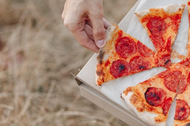 Männliche hand nimmt pizza aus der schachtel