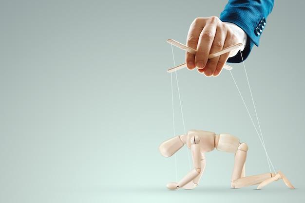 Männliche hand, puppenspieler steuert die puppenpuppe mit schnüren. eine puppe auf den knien. das konzept der weltverschwörung, weltregierung, manipulation, kontrolle.