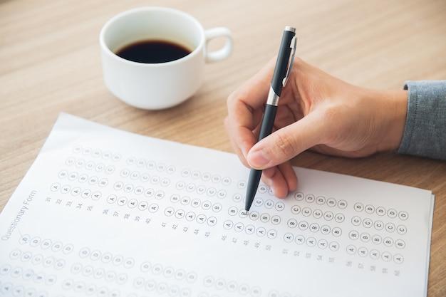 Männliche hand questionary form mit stift zu beantworten