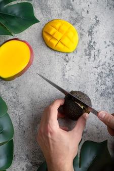 Männliche hand schneidet frische reife avocado mit messer auf steinhintergrund.