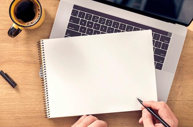 Männliche hand schreibt in notizbuch online-arbeit oder bildungskonzept