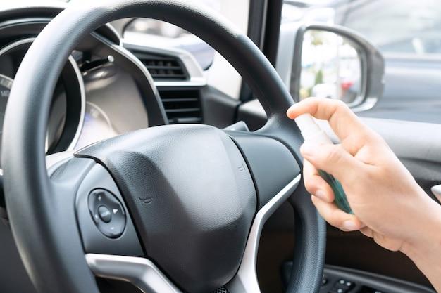 Männliche hand sprüht alkohol auf autolenkrad zur desinfektion.