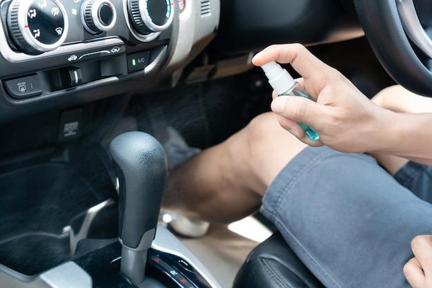 Männliche hand sprüht alkohol zum getriebe zum desinfizieren. oberflächen während des coronavirus reinigen