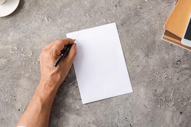 Männliche hand und leeres papierblatt auf grau