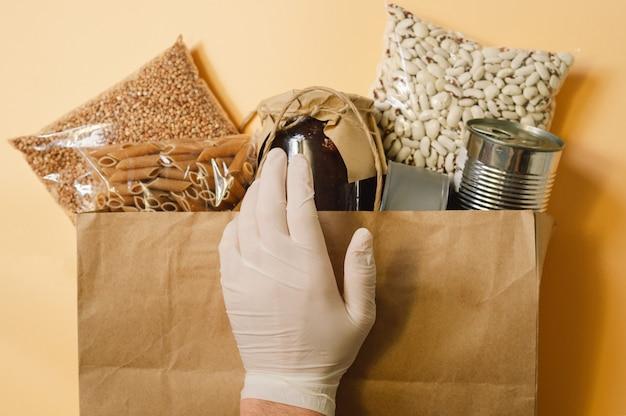 Männliche hand und papiertüte mit lebensmittelversorgungskrise für quarantäne