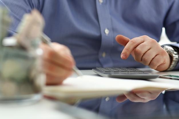Männliche hand unter verwendung des taschenrechners, der finanzielle ausgaben zählt