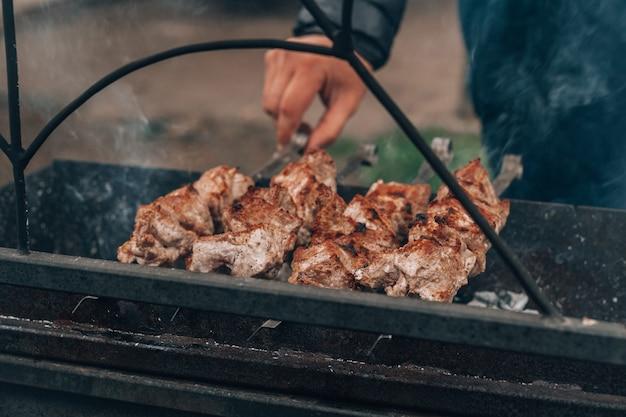 Männliche hand verwandelt rohes gebratenes fleisch auf spieße und wird auf holzkohlegrill gekocht. grillen im freien kochen