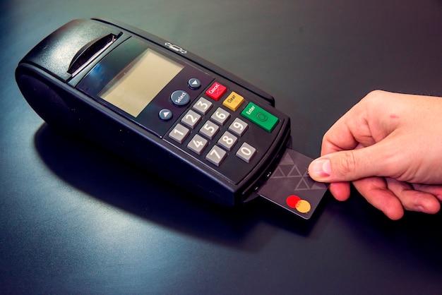Männliche hand wählt pin-code auf pin-pad von karte maschine oder pos terminal mit eingelegten leere weiße kreditkarte isoliert auf weißem hintergrund. zahlung mit kreditkarte - kaufmann hält pos terminal.