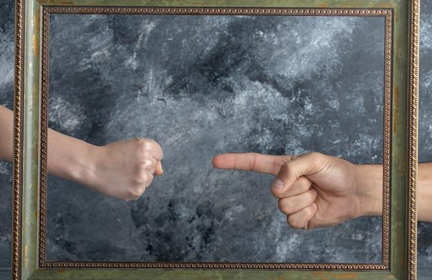 Männliche hand zeigt auf weibliche hand in der mitte des bilderrahmens.