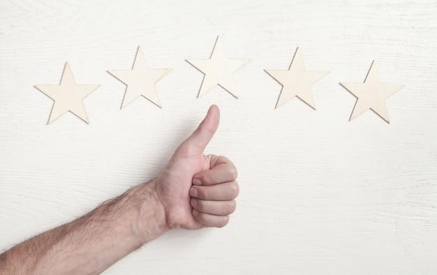 Männliche hand zeigt daumen hoch und fünf-sterne-bewertung. kundenservice erfahrung und zufriedenheit