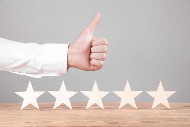 Männliche hand zeigt daumen hoch und fünf-sterne-bewertung
