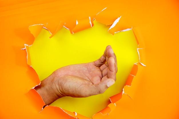 Männliche hand zerrissener orange papierhintergrund