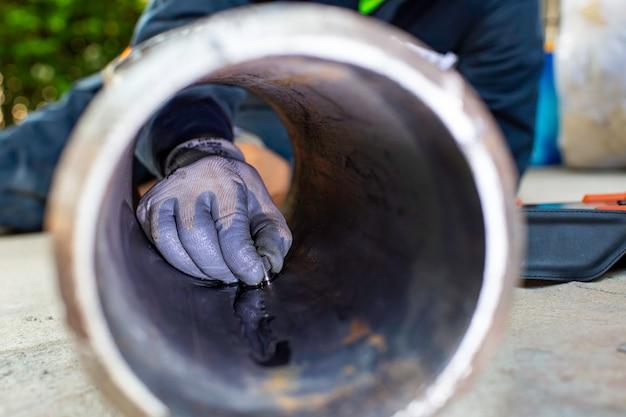 Männliche handarbeiterinspektion ultraschalldicke rohrstahlmaterial durch rost verursacht alte verrostete eisenhintergrundkonzepte, männlicher handnahaufnahmebereich