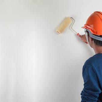 Männliche handmalereiwand mit der farbenrolle, erneuernd mit weißer farbfarbe.
