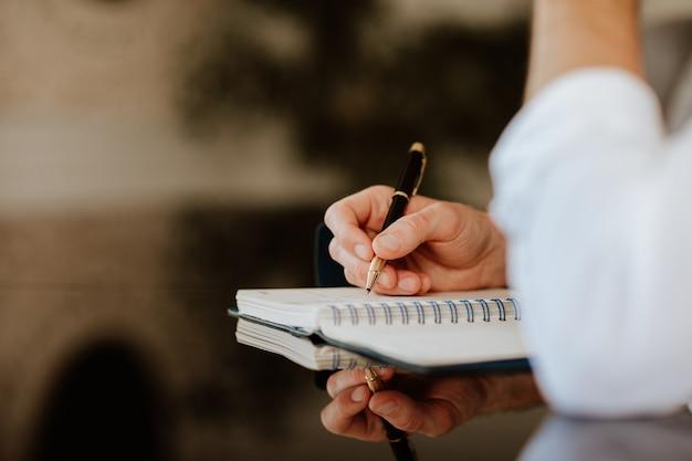 Männliche handschrift in anmerkung platziert auf dunklem glastisch. geschäftskonzept. fokus liegt auf der hand. platz kopieren.