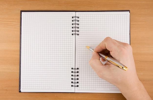 Männliche handschrift mit stift auf geprüftem notizbuch