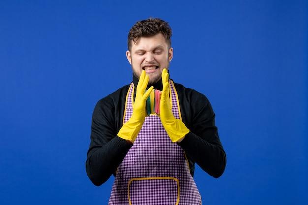 Männliche haushälterin der vorderansicht drückt schwämme auf blauem raum