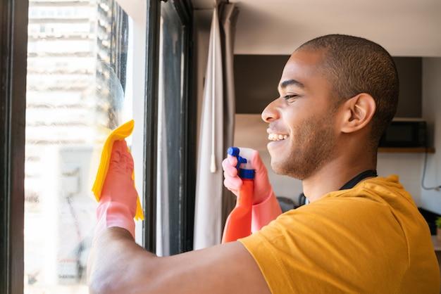 Männliche haushälterin, die glasfenster zu hause reinigt.