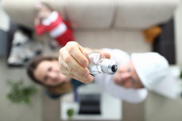 Männliche haushälterin hilft, glühlampe zu ändern.