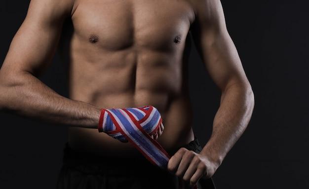 Männliche kämpferhand der nahaufnahme mit verbänden. die fäuste eines kämpfers geballt vor einem kampf oder training in einem sportstudio.