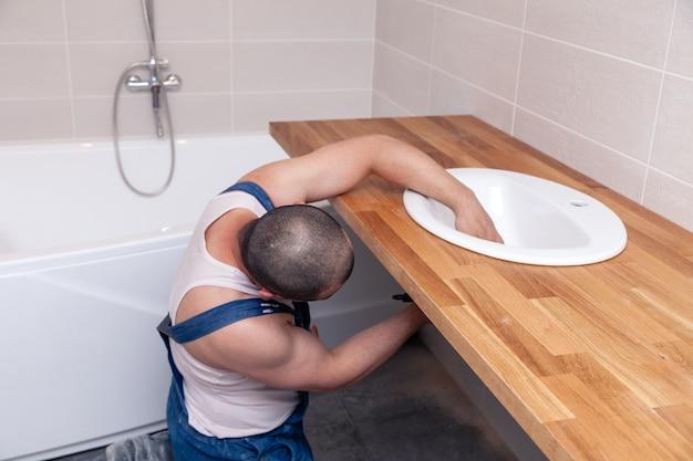 Männliche klempnerarbeitskraft der nahaufnahme in der blauen denimuniform, overall, wanne im badezimmer mit fliesenwand reparierend. professioneller sanitärreparaturservice, installation von wasserleitungen, kanalisation am mann