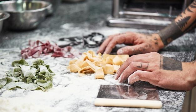 Männliche kochhände mit tätowierungen, die italienische pasta auf dem küchentisch mit mehl fertig machen
