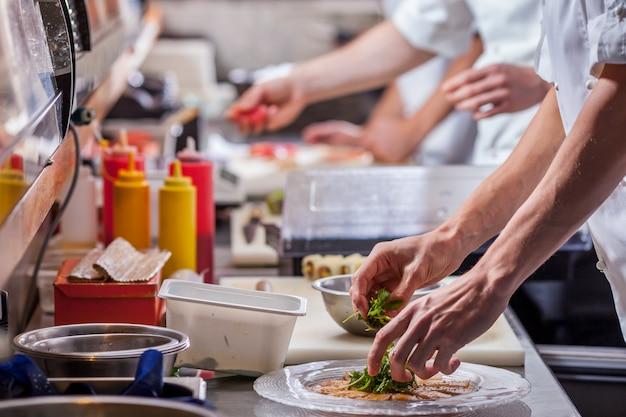 Männliche köche bereiten mahlzeiten vor. speise- und getränkekonzept