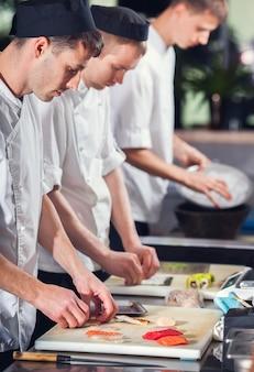 Männliche köche bereiten sushi vor. speise- und getränkekonzept