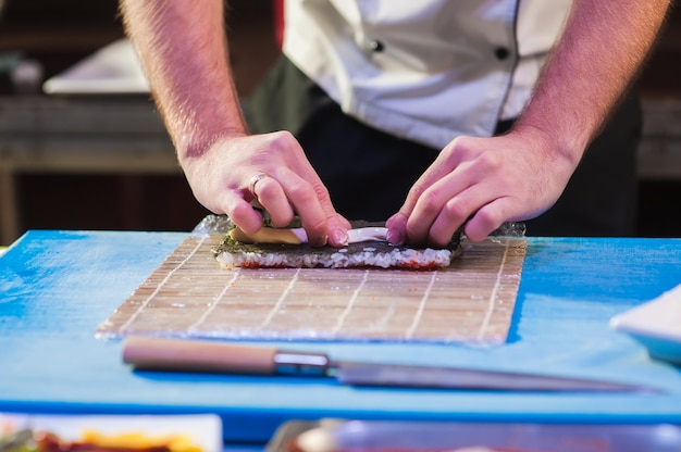 Männliche köche bereiten sushi vor