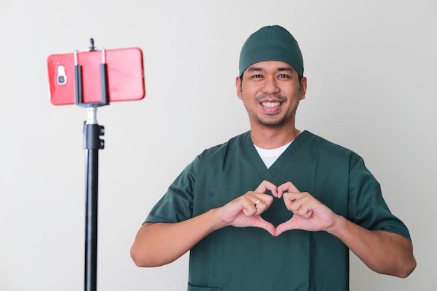 Männliche krankenhauskrankenschwester, die liebesherzzeichen vor dem handy gibt. online-beratungskonzept