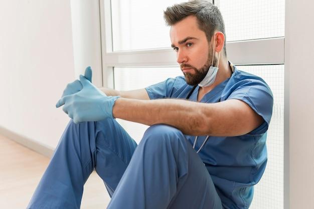 Männliche krankenschwester, die chirurgische handschuhe trägt