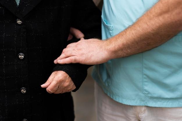 Männliche krankenschwester, die den arm der älteren frau hält