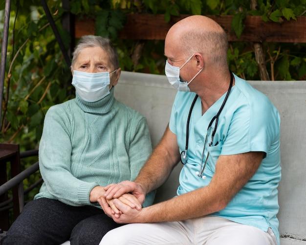Männliche krankenschwester, die die hände der älteren frau hält