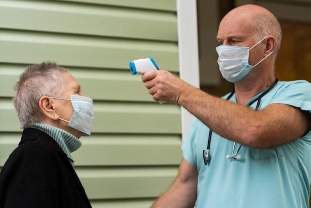 Männliche krankenschwester, die die temperatur der älteren frau mit thermometer prüft