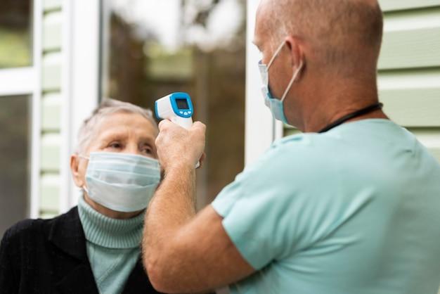 Männliche krankenschwester, die die temperatur der älteren frau prüft