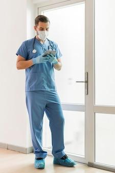 Männliche krankenschwester, die medizinische handschuhe und maske trägt