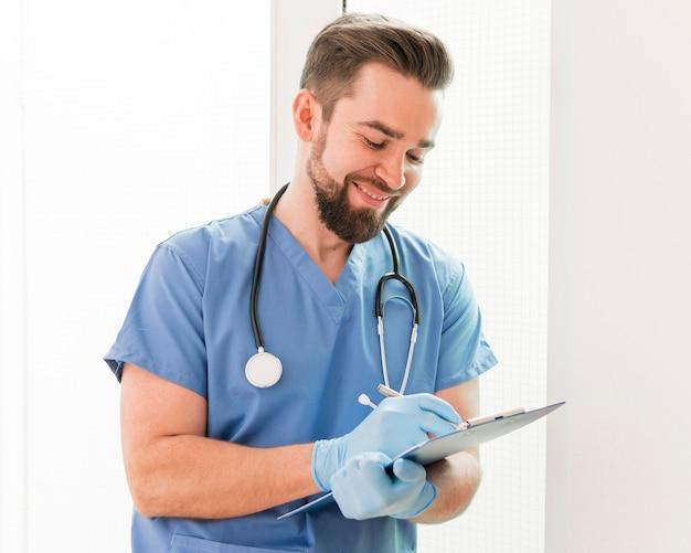 Männliche krankenschwester, die medizinische notizen schreibt