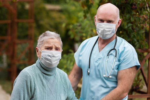 Männliche krankenschwester, die mit älterer frau am pflegeheim aufwirft