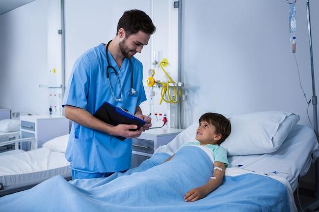 Männliche krankenschwester, die mit dem patienten während des besuchs in der station interagiert