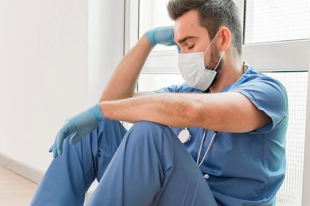Männliche krankenschwester, die nach einer langen schicht eine pause macht