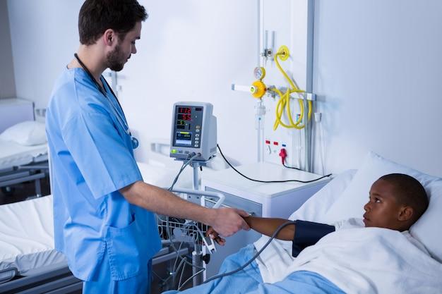 Männliche krankenschwester, die patientenblutdruck in der station prüft