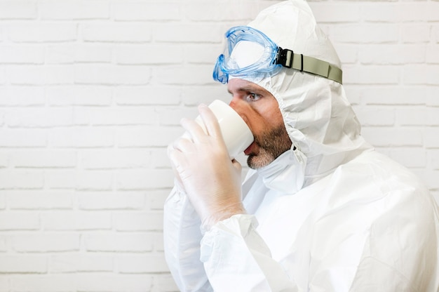 Männliche krankenschwester, die schutzanzug und arbeitskleidung trägt, die eine tasse kaffee während der pause trinkt