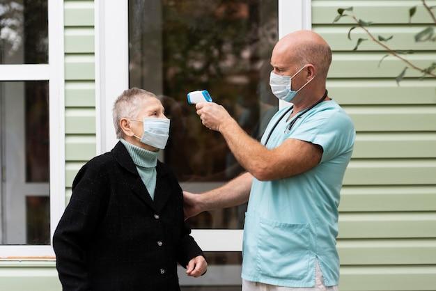 Männliche krankenschwester mit einem thermometer, um die temperatur der älteren frau zu überprüfen