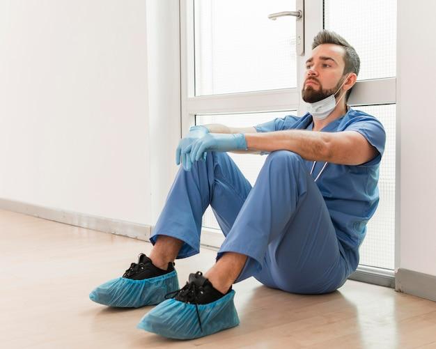 Männliche krankenschwester müde nach einem langen arbeitstag