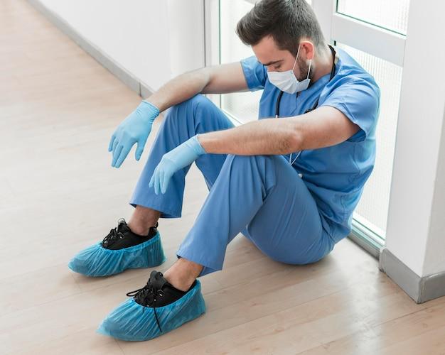 Männliche krankenschwester müde nach langer schicht im krankenhaus