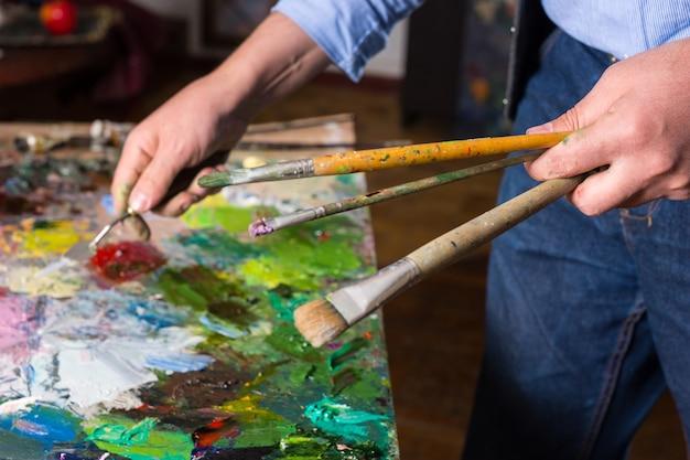 Männliche künstlerhand, die paletten-khife und pinsel unter bunter palette in seinem atelier hält
