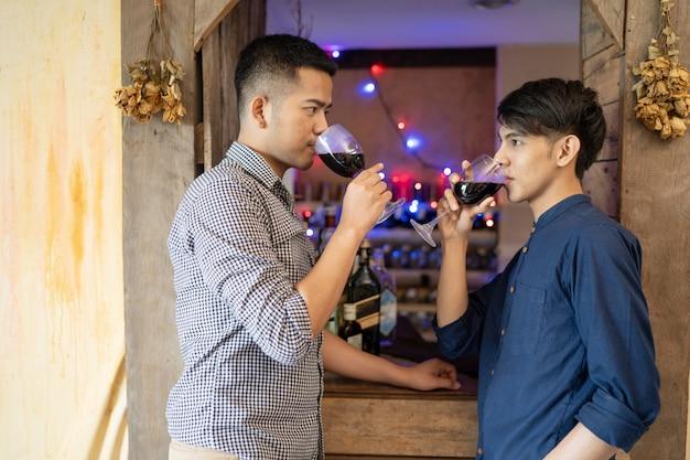 Männliche lgbt-paare trinken wein feiern sie die weihnachtszeit